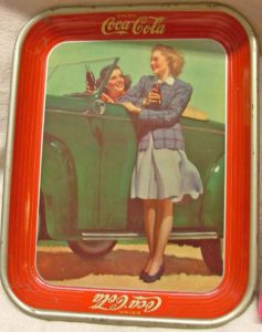 1942 Coca Cola Advertising Tray with woman at driver's wheel of a green convertible car and another woman standing and talking to her.