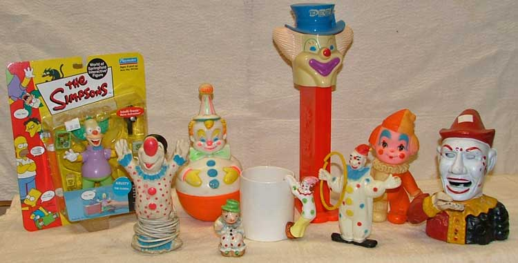L-R The Simpsons Krusty the Clown, clown nightlight, Roly Poly clown, clown salt shaker, clown cup, giant clown PEZ dispenser - Peter Pez, plastic clown with hoop, squeak toy clown, cast-iron clown bank