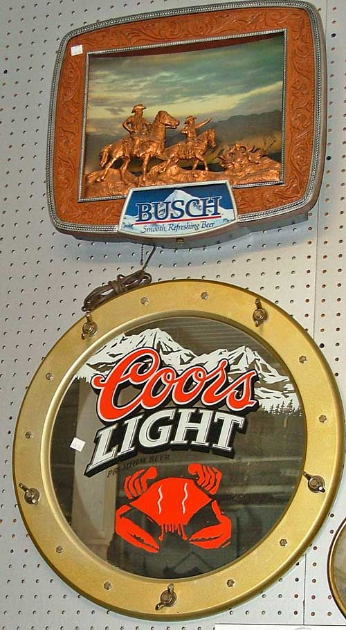 two advertising signs include top - Busch beer with two people on horseback on a mountain top and bottom - Coors Light porthole with crab