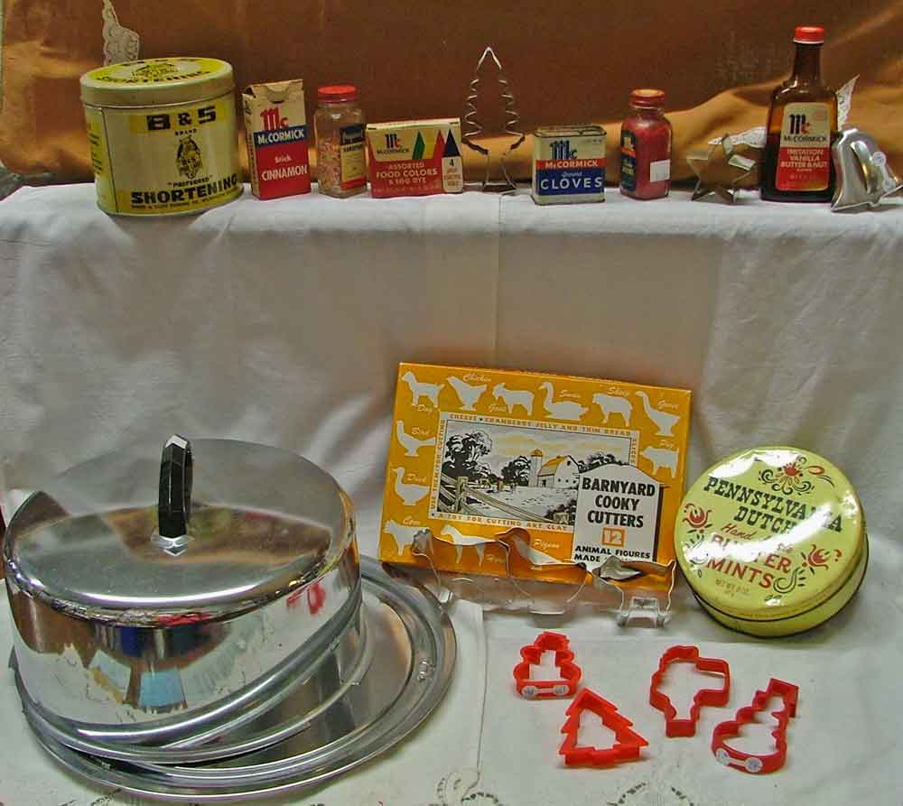 Baking memorabilia including B&S brand shortening tin, old spices and food coloring, a variety of metal and plastic cookie cutters, a cake platter and cover, and a PA Dutch handmade Butter Mints tin