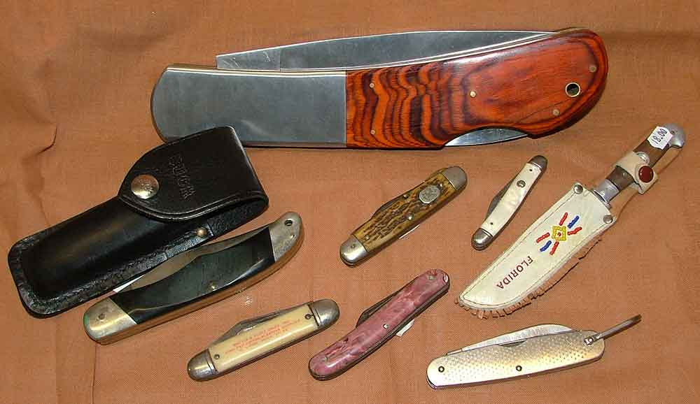 "A variety of Knives available at Bahoukas in Havre de Grace - Buck Knife w/black case, Boy Scout Knife 1950s, Imperial Pocket knife, a Florida souvenir knife with compass on handle, Johnston Mfg peralized handle knife with 2"" blade, and a US Military knife by Camillus 1977"