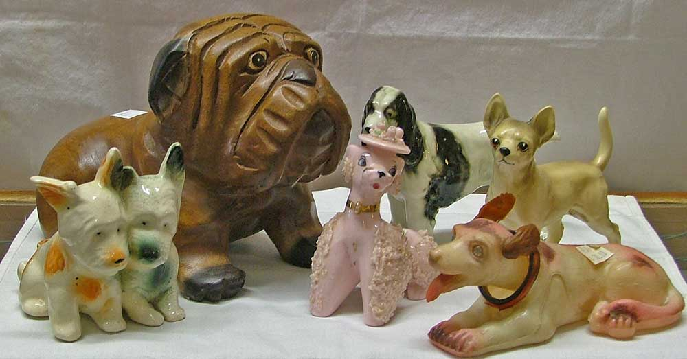 Dog figurines include a wooden dog, Sprainger Spaniel porcellain, Scottie Dog Planter, pink spaghetti Poodle, a Chihuahua and a plaster nodder dog all at Bahoukas in Havre de Grace