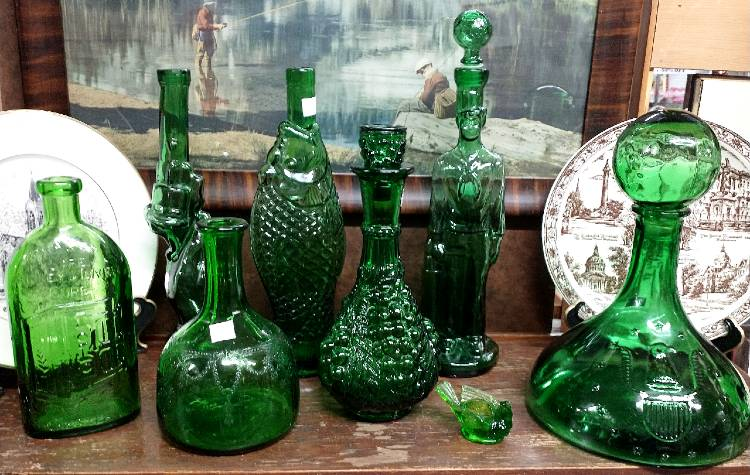 a wonderful collection of green glass figural bottles that include a fish, a gun, and more available at Bahoukas.