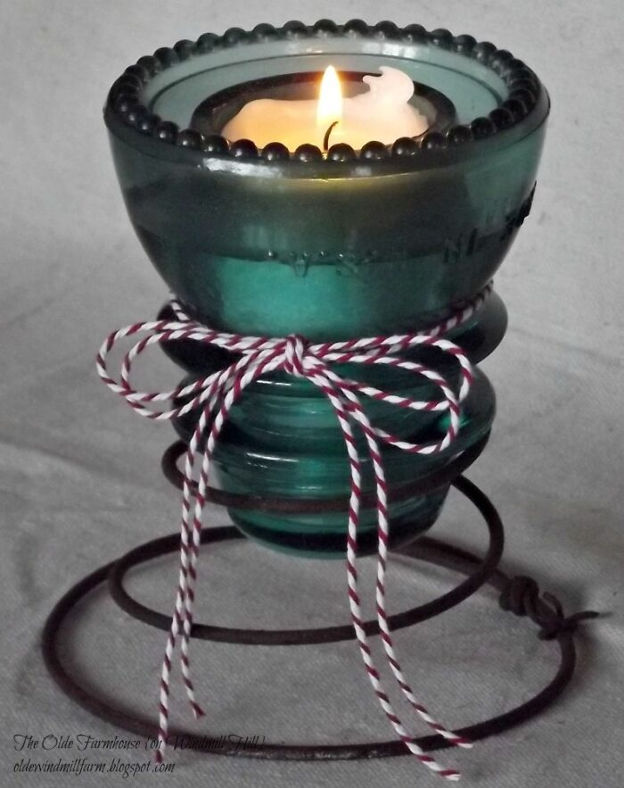 from pickledbarrel.com - a beautiful example of creating a candle holder for wedding decor from an old glass insulator.