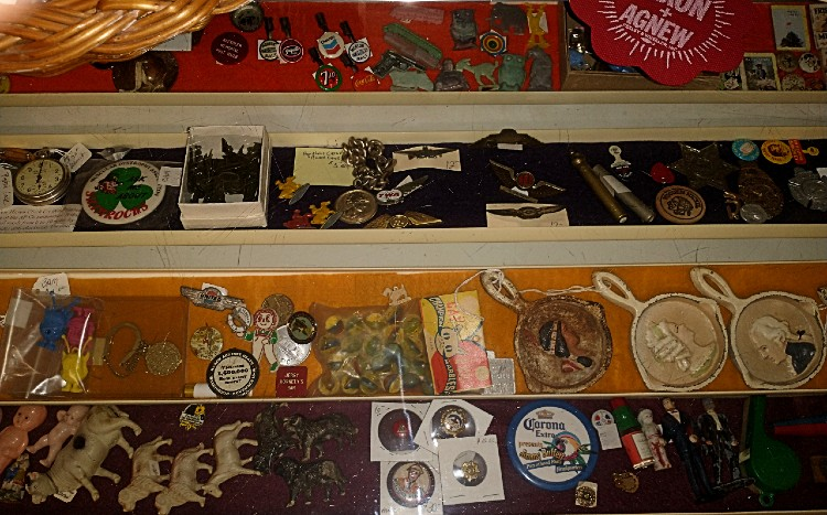 A case of tinies - small collectible items such as pins, badges, small figures, tokens, etc