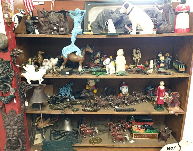 shlelves of cast iron figures - vintage, collectible and reproduction - at Bahoukas Antiques